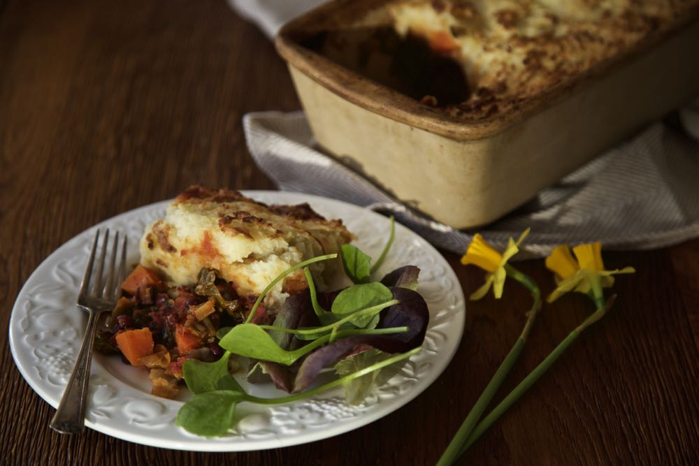Red Dragon Pie with salad on a white plate, alongside daffodils and the rest of the pie in a stoneware dish.