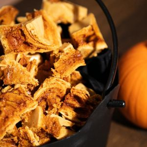 Cinder Toffee pieces in a black cauldron next to a pumpkin.