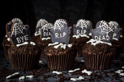 Tombstone cupcakes with cobwebs and bones.