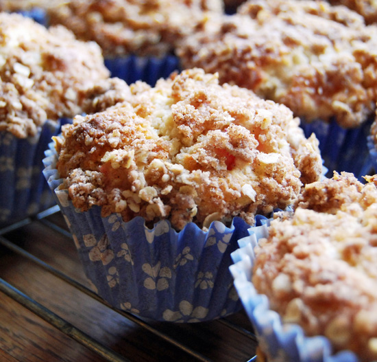 Rhubarb crumble muffins in paper cups, sat on a wire cooling rack.