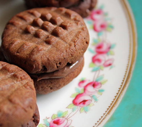 Fork sandwich biscuits with Nutella on a decorative plate.