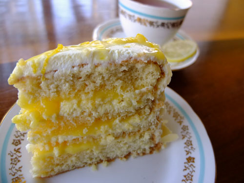 A slice of the finished lemon cream cake on a decorative plate, along with a cup of tea.