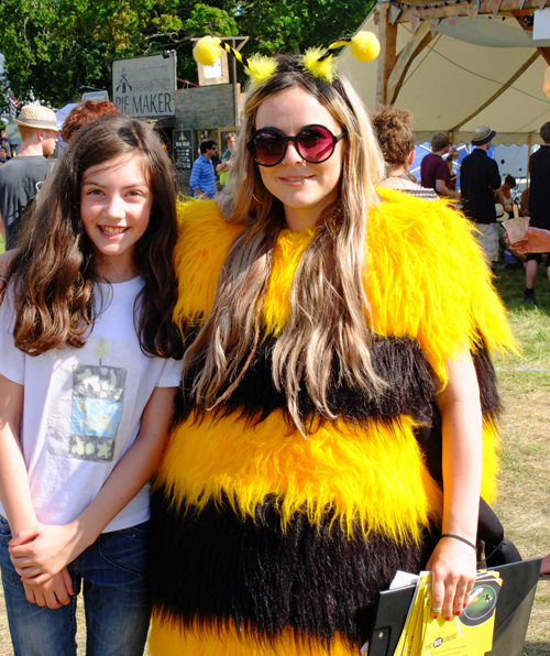 Young girl at a festival, along with a woman dressed as a bee.