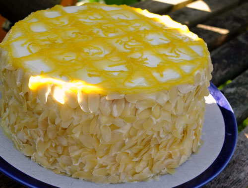Lemon cream cake with a lemon rind topping and a lining of almonds around the sides.