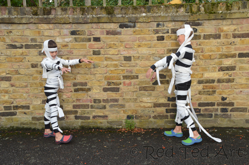 Boys in mummy costumes walking with outstretched arms.