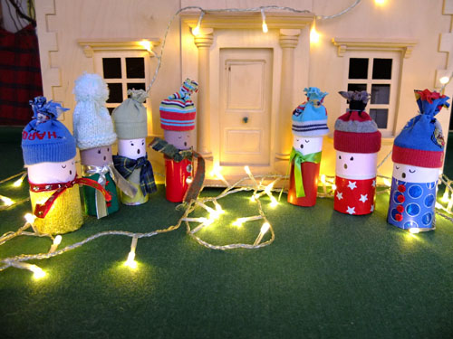 Toilet roll carol singers outside of a dolls' house.