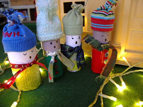 Toilet roll carol singers surrounded by fairy lights.