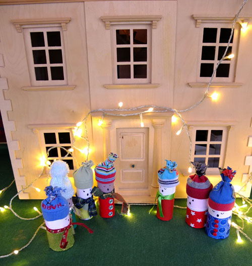 Toilet roll christmas carol singers together outisde of a dolls' house, lit by fairy lights.