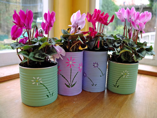 Flowers in food tins painted in pastel colours.