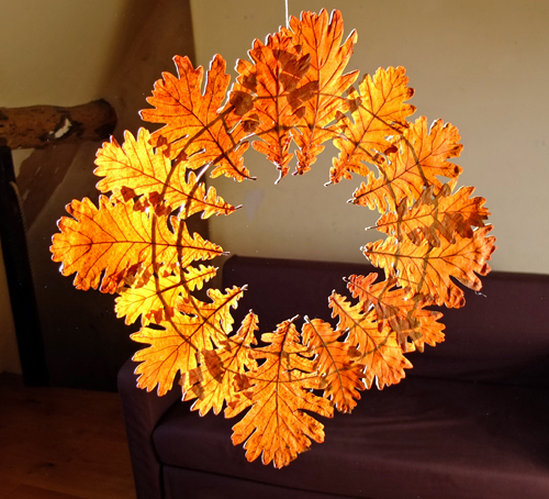 A finished autumn leaf wreath hanging from a string.