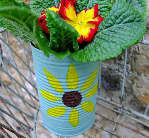 A plant growing in a tin with a sunflower painted on the front.