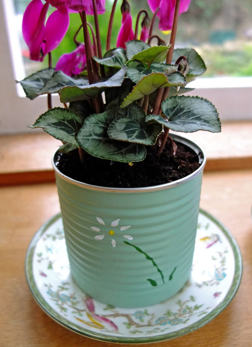 A plant growing in a painted tin, with a flower painted on the front.