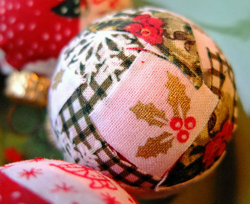 Closeup of a bauble with snowflake and holly patterned fabric.