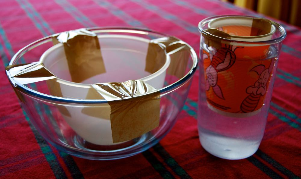 A bowl and jug with smaller containers suspended in them using parcel tape.