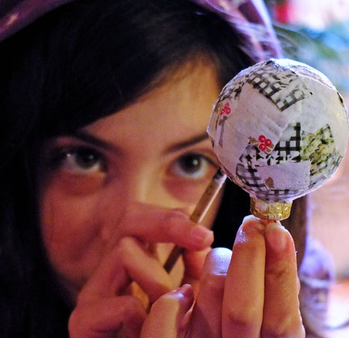 Young girl gluing fabric scraps to the outside of a bauble.