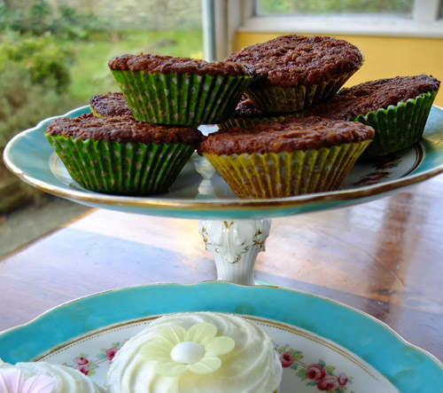 Carrot buns without icing on a decorative cake stand.