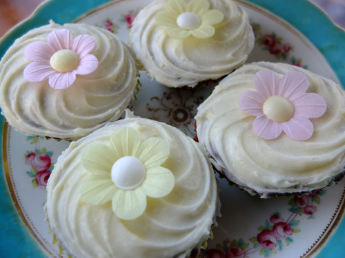 Carrot buns with decorative icing and edible paper flowers on a cake stand.