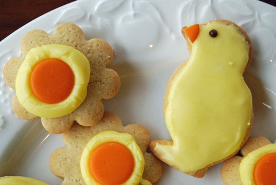 Iced easter chick and flower biscuits on a white plate.