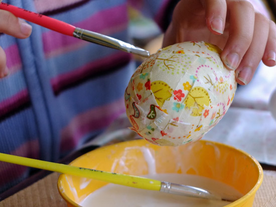 Gluing fabric scraps to a polystyrene egg.