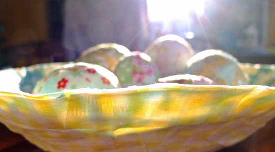 Sun shining through the bowl to show the different colours of fabric that were used to make it.