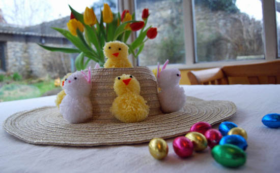 Easter bonnet decorated with pompom chicks and rabbits, with chocolate mini eggs in the foreground.