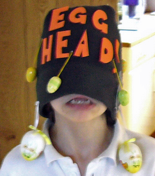 Egg head easter bonnet, with eggs dangling from string and the wearer grimacing.