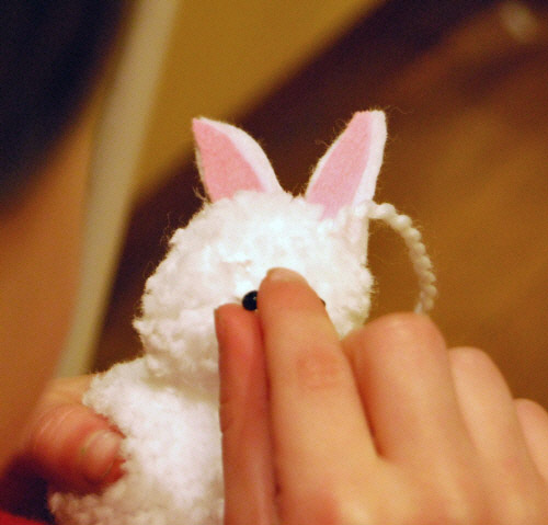 Adding the eyes to a pompom with bunny ears.
