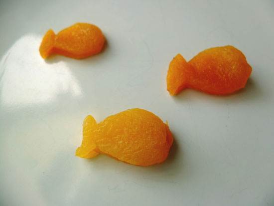 Apricot goldfish on a white plate.