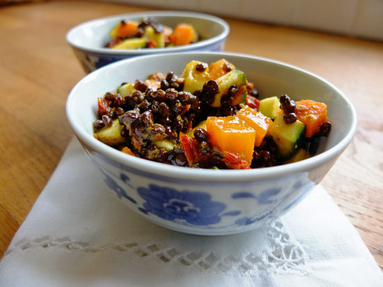 Two bowls of beluga lentil salad with carrot and courgette.
