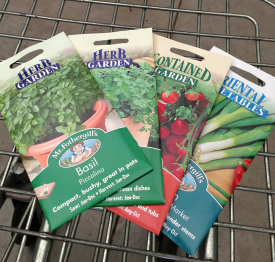 Four different packets of vegetable and tomato seeds in a shopping trolley.