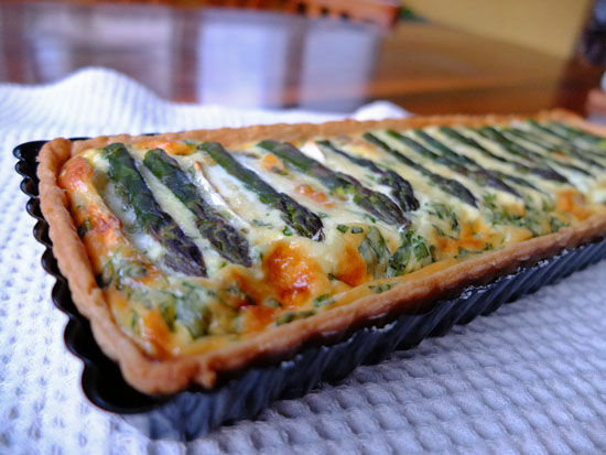 Asparagus quiche with a row of whole asparagus spears making up the topping.