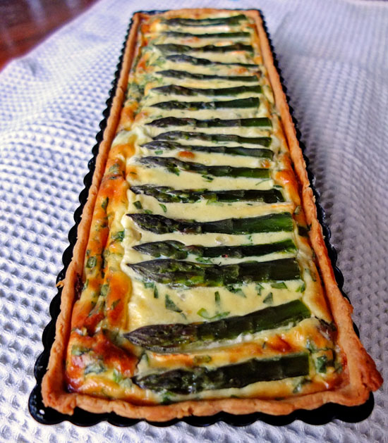 Asparagus quiche with golden brown baked cheese and whole spears of asparagus.