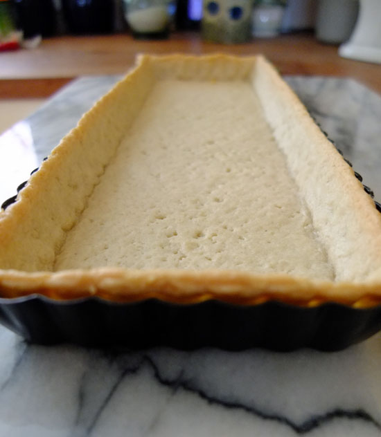 Pastry case for the quiche, sat ready in a rectangular tray.
