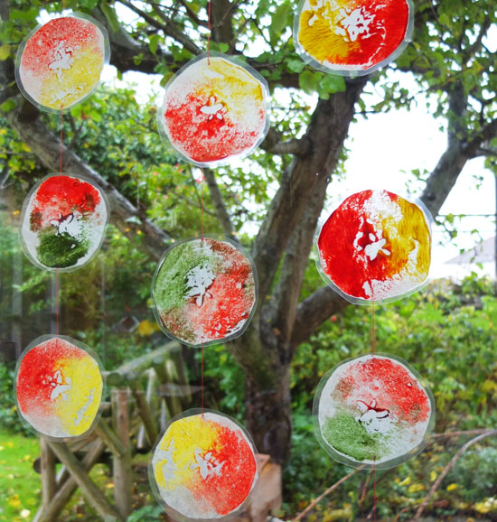 A collection of apple prints, linked together by string and hanging in front of a window to the garden.