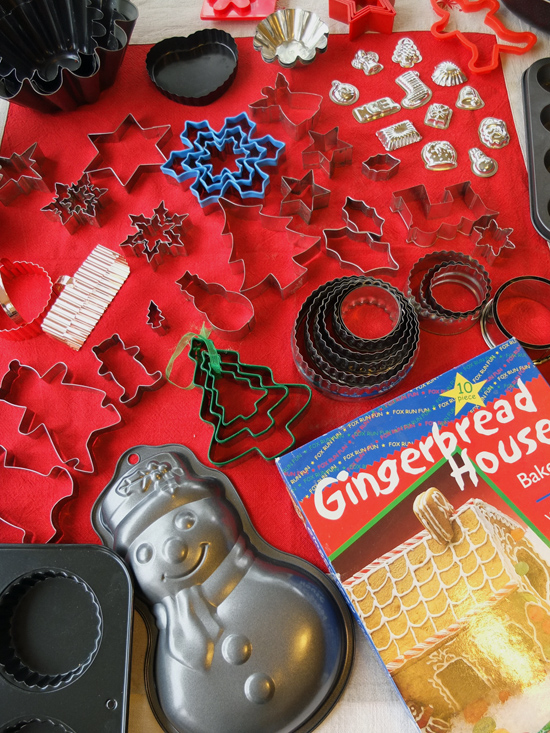 Large collection of christmas cookie cutters and moulds laid out on a red cloth.