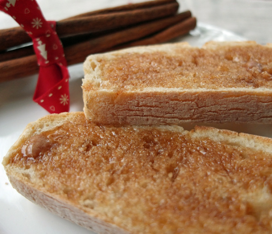 Cinnamon butter on white toast with cinnamon sticks in the background.