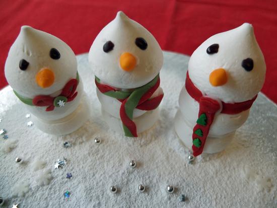 Three merangue snowmen on an icing sugar snowfield.