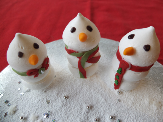 Little meringue snowmen with icing scarves.