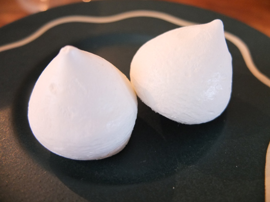 Two mini meringues on a dark saucer.