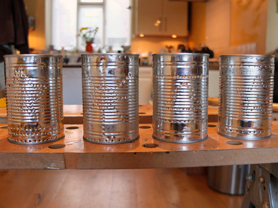 Tin cans with festive patterns made of small holes.