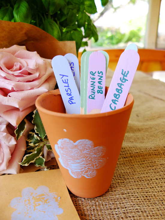 Decorated plant pots filled with ice lolly plant labels.