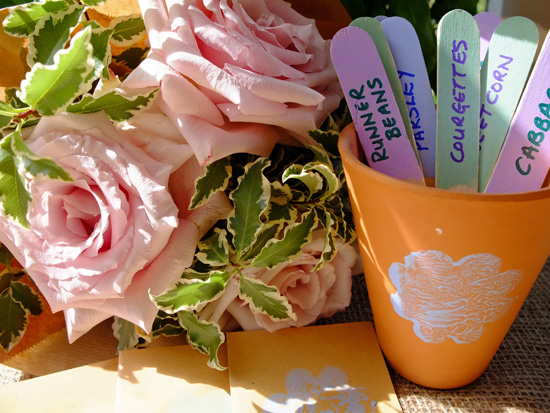 Pink roses and a pot full of plant labels made from coloured ice lolly sticks.