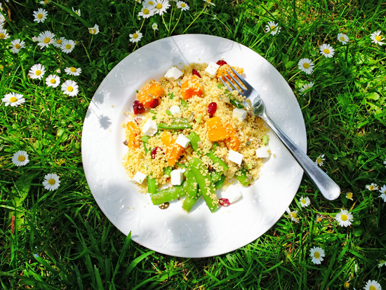 Couscous salad with butternut squash and feta, on the lawn in the shade of a tree.