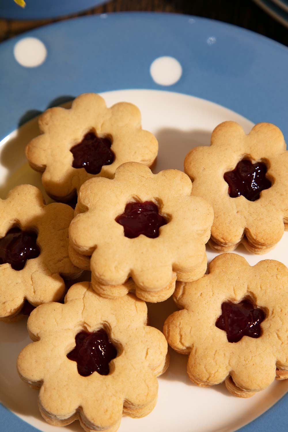 Flower shaped jammy dodgers on a blue and white spotty plate.