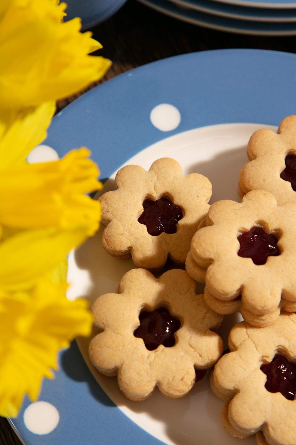 Homemade Jammy Dodgers on a blue and white spotty plate with a bunch of daffodils.