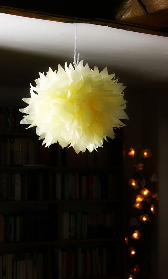 Pom pom hanging from the cieling by its pipe cleaner.