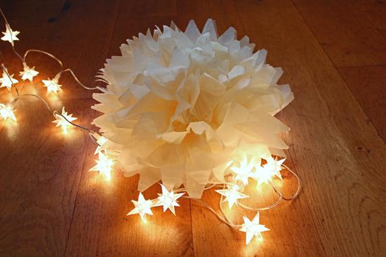 Tissue paper pom pom lit by fairylights.