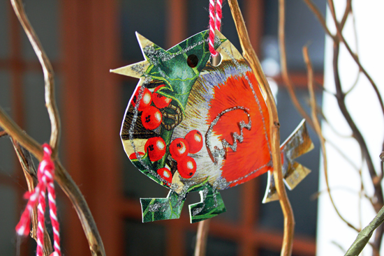Christmas robin cut from a card with holly and berries.