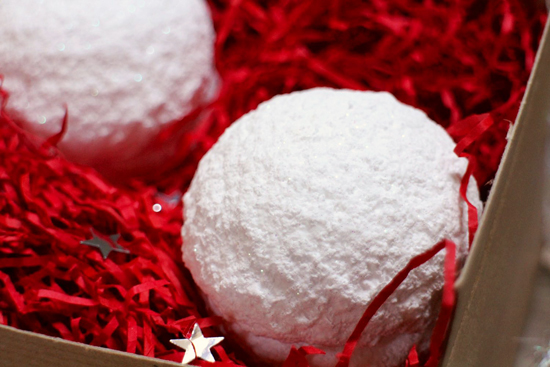 Snowball bath bomb on a bed of red tissue paper strands.