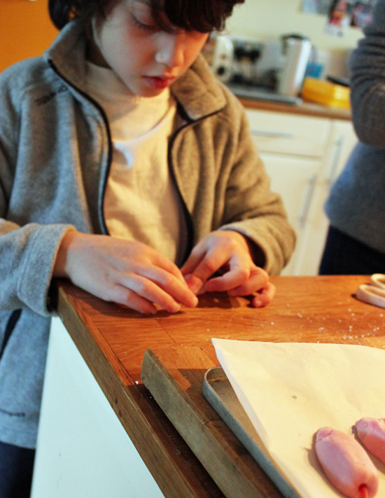 Young boy shaping a sugar mouse by hand.